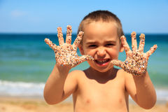 Little boy showing sandy hands Stock Images