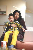 Little boy showing something to his mother on laptop. African American women and her son using laptop at home Royalty Free Stock Photography