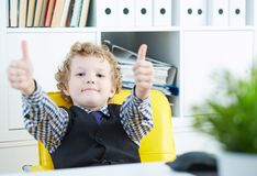 Little boy showing thumb up looking into camera. The boy is sitting in the boss`s chair in the office. stock photos