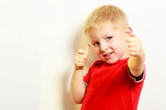 Little boy showing thumb up success hand sign gesture. Royalty Free Stock Photo