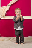 Little boy showing thumbs up indoors Stock Photo
