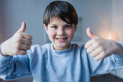 Little boy showing thumbs up and smiling at camera stock photography