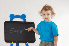 Little boy shows Einstein's formula on blackboard Royalty Free Stock Photography