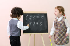 Little boy shows by finger figures at chalkboard for cute girl Royalty Free Stock Images