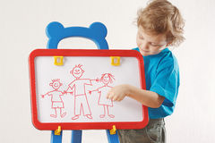 Little boy shows his family painted on whiteboard Royalty Free Stock Photos