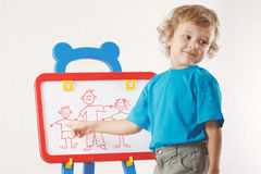 Little boy shows his family painted on whiteboard Stock Image