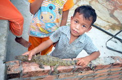 Little boy shows little crocodile. On a crocodile farm in Siem Reap Cambodia which ladeet his seven Royalty Free Stock Photo