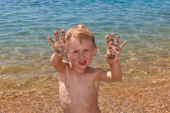 Little boy shows palms in sand Royalty Free Stock Photography