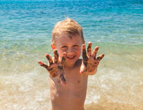 Little boy shows palms in sand Royalty Free Stock Photos
