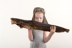 The little boy shows what a big fish he caught in the river. The concept of organic food.  Royalty Free Stock Images