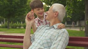 Little boy shuts grandpa`s eyes with his hands stock images