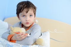 The little boy is sick. He lies in bed. Stock Photo