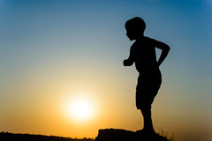Little boy silhouetted against the sunset Royalty Free Stock Photos