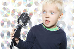 Little boy singing. Small, pretty boy singing to microphone stock images