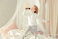 Little boy singing. Little boy standing on the bed and singing stock photos