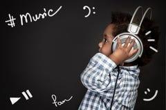 Little boy sings baby songs. Cute little african american boy wearing earphones, listening and recording baby songs, portrait over blackboard background, happy royalty free stock image