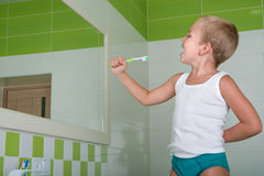 Little boy sings the song in the toothbrush in the bathroom.The future singer. Boy sings the song in the toothbrush in the bathroom Royalty Free Stock Photo