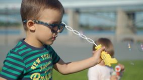 Little Boy with Sister Blowing Soap Bubbles stock footage