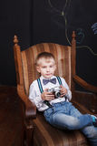 A little boy sit in armchair and holds photo camera in his hands Stock Photo