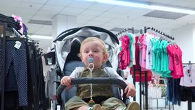 Little boy sit in baby buggy in a clothing store. Little boy in a clothing store stock video footage