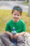 Little boy sit with bottle of water Royalty Free Stock Photography