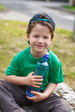 Little boy sit with bottle of water Stock Photography