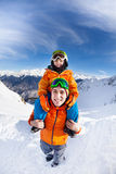 Little boy sit on fathers shoulders in mountains Stock Image