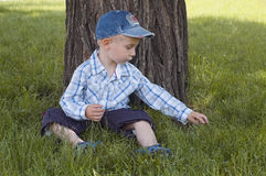 Little boy sit on a lawn and play Royalty Free Stock Images