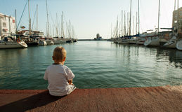 Little boy sits alone in the port Royalty Free Stock Images