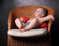 little boy sits on an armchair Stock Images