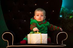 Little boy sits in armchair with Christmas gift box. stock photos