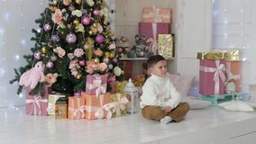 Little boy sits on the background of a christmas interior in a New Year`s studio. Little boy sits on the background of a christmas interior stock video footage