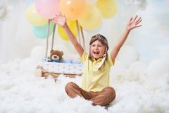 A little boy sits in a balloon basket in the clouds, pretending to travel and fly with an Aviator hat for a concept of creativity royalty free stock photos