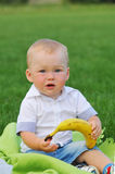 Little boy sits with banana Stock Photography