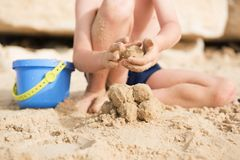 A little boy sits on the beach in the sand. And sculpts sand lumps Stock Images