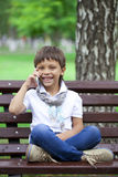 A little boy sits on a bench and calling by mobile phone Stock Image