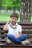 A little boy sits on a bench and calling by mobile phone Royalty Free Stock Photography