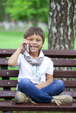 A little boy sits on a bench and calling by mobile phone Royalty Free Stock Image