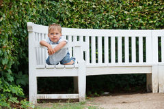 Little boy sits on a bench in a park Royalty Free Stock Photography