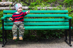 Little boy sits on bench in a park. Little boy in a striped sweater with red and black stripes sitting on a green bench. and points in the direction. He is Royalty Free Stock Photos