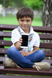 A little boy sits on a bench and showing mobile phone screen Stock Photography