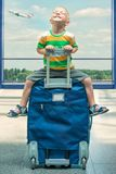 A little boy sits on the big suitcase at the airport.Waiting for the flight. royalty free stock image