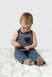 Little boy sits on blanket playing with cellphone Royalty Free Stock Images