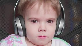 A little boy sits in a chair and listens to music through headphones. Face close up stock video