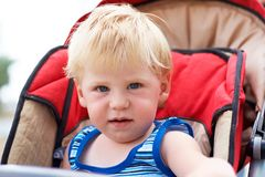 The little boy sits in a children's carriage Stock Photography
