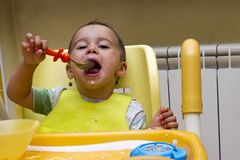 Little boy sits in a children`s chair and studies have meals. The first independent actions of the child. Little baby eats with a spoon soup plate. He sits on a Stock Photos