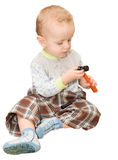 The little boy sits and considers a toy plastic hammer. The isol Royalty Free Stock Photos