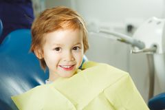 Little boy sits on dentist`s chair in good mood after dental procedures. Young patient with healthy teeth. Tooth, caries, superficial Stock Images