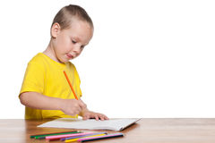 Little boy sits at the desk and write Stock Photo