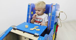 A little boy sits in a development car and eats cookies. A functional Montessori toy. Fine motor skills. Sensory sensitivity stock video footage